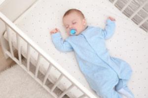 bébé dort sur le dos dans son lit avec une tétine dans la bouche