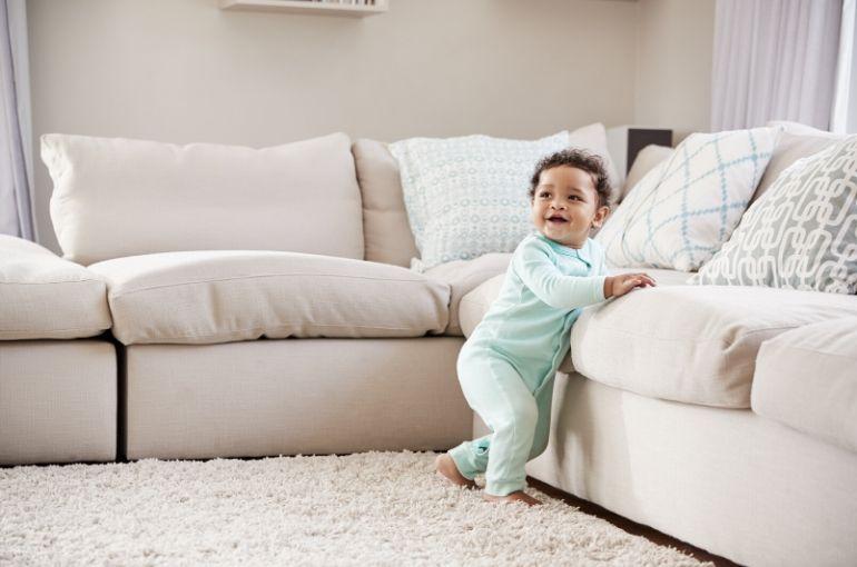 bébé debout se tient au canapé